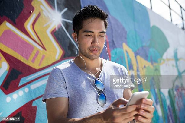 Asian man in front of graffiti reading phone.