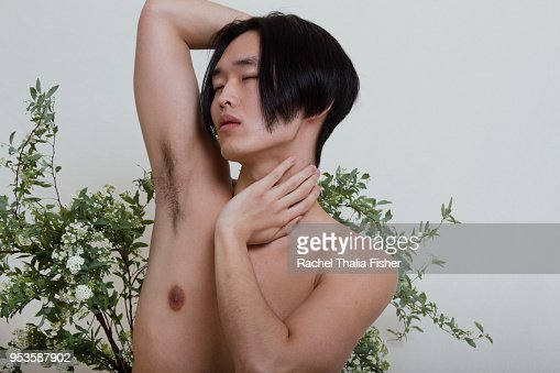 Asian man in thoughtful pose in studio with flowers behind him