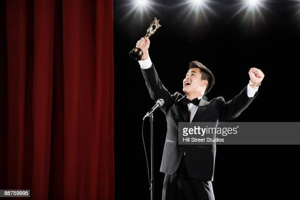 asian man in tuxedo holding trophy overhead at microphone - awards ceremony stock pictures, royalty-free photos & images