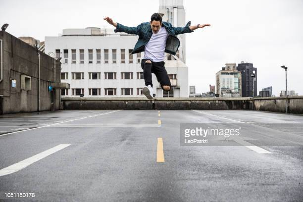 asian man in urban exploration on the roofs of the city - leap day stock pictures, royalty-free photos & images