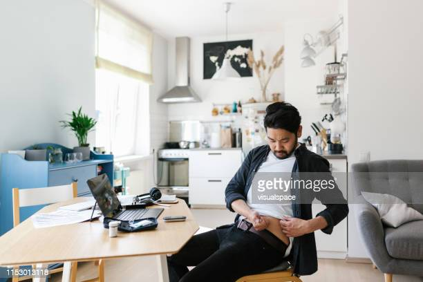 asian man injecting insulin while working from home office - insulin stock pictures, royalty-free photos & images