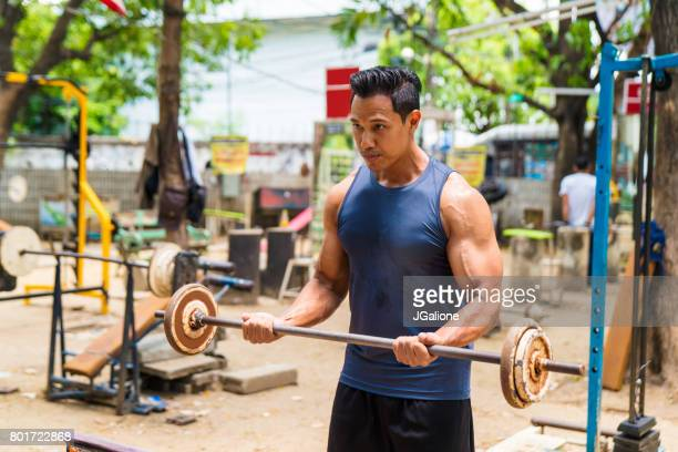 Asian man lifting weights in an outdoor gym
