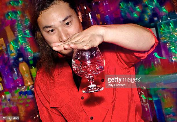 Asian man looking at a glass goblet suspended from the bottom of his hand.