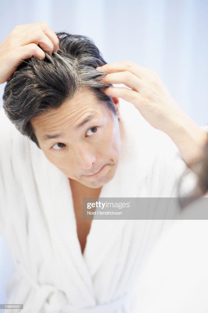 Asian man looking at gray hair in mirror : ストックフォト