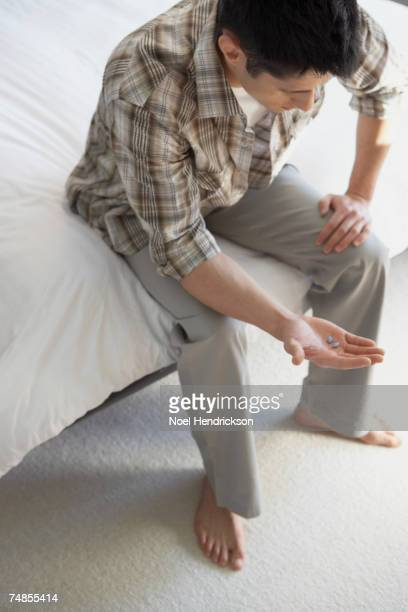 asian man looking at pills in hand - viagra stock photos and pictures