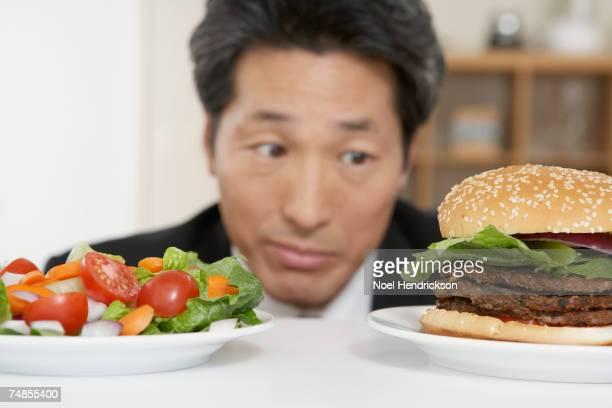 asian man looking at salad and hamburger - 体への関心 ストックフォトと画像