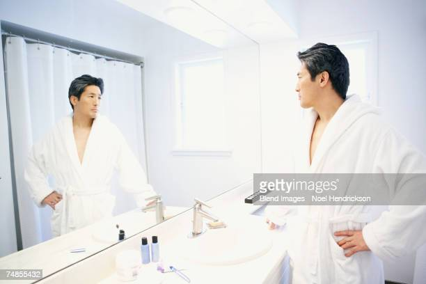 Asian man looking in bathroom mirror