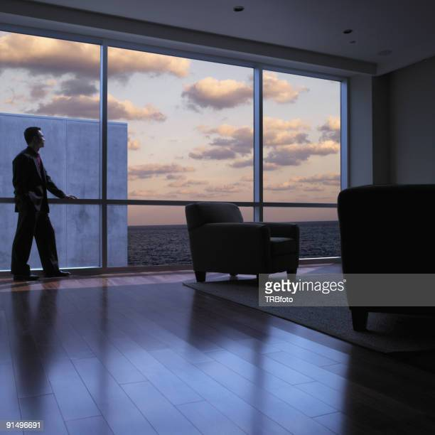 Asian man looking out window at dusk