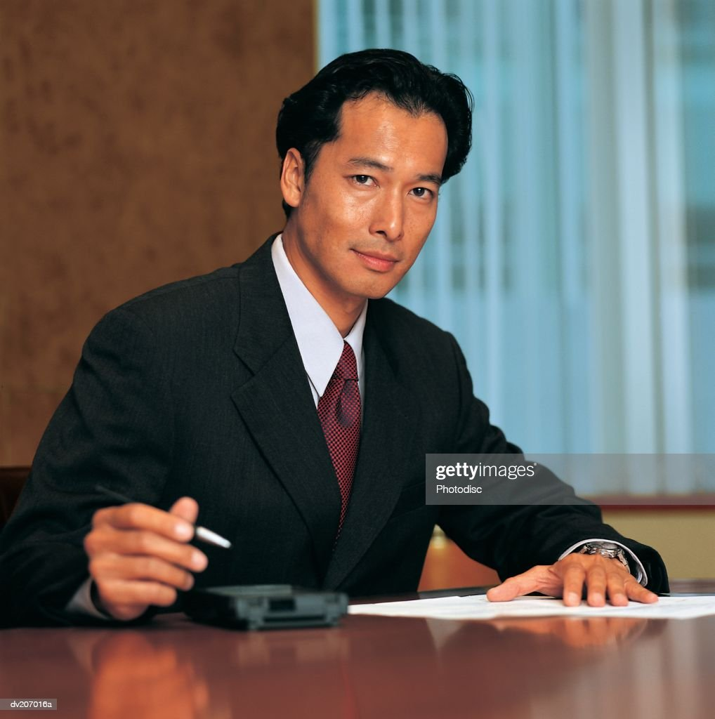 Asian man looking up from papers : Stock Photo