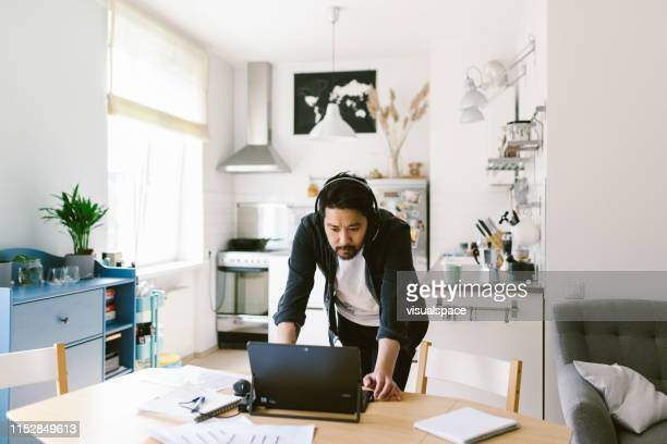 asian man looks at the computer during video conference call - mid adult men stock pictures, royalty-free photos & images