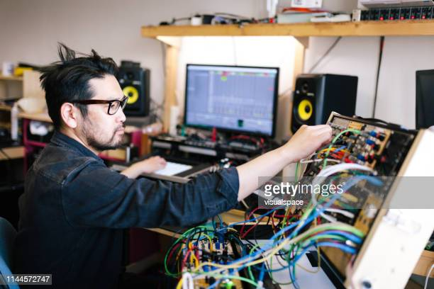 asian man making analog electronic music with self made instruments - producer stock pictures, royalty-free photos & images
