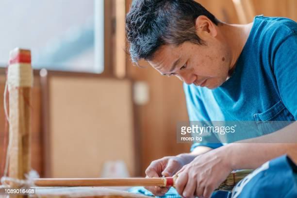 アジア人の男性が彼の作業スペースでほうきを作る - 伝統 ストックフォトと画像