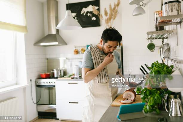 asian man making chashu pork with the help of digital cookbook - asian food stock pictures, royalty-free photos & images