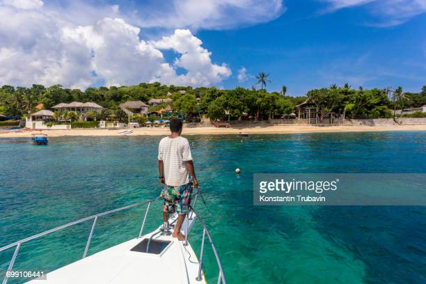 Asian man on a yacht at ocean near Nusa Lembongan island,Bali,Indonesia.