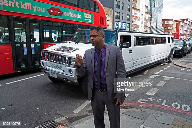 Asian man on Commercial Road in the East End looks down the street as a white stretch limousine Hummer passes containing a party of people in London...