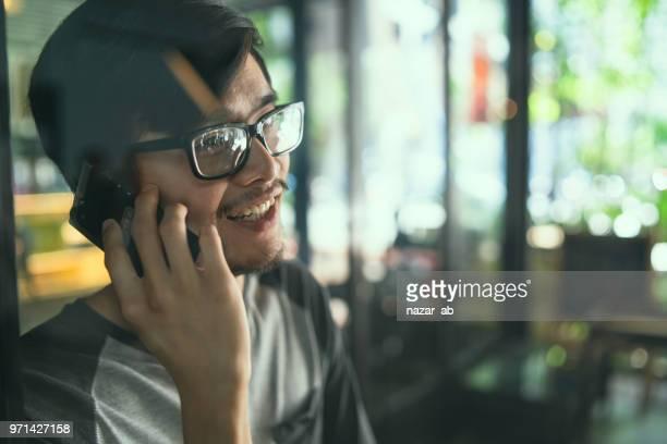 Asian man on phone talking.