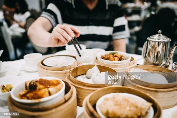 Asian man picking up siu mai with chopsticks and enjoying a variety of freshly made dim sum in restaurant