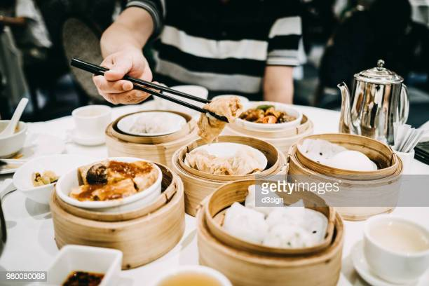 asian man picking up steamed beancurd roll with chopsticks and enjoying a variety of dim sum in restaurant - comida china fotografías e imágenes de stock