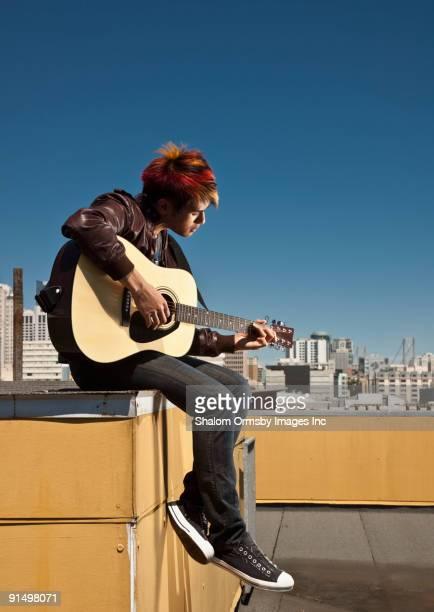 Asian man playing guitar on urban rooftop