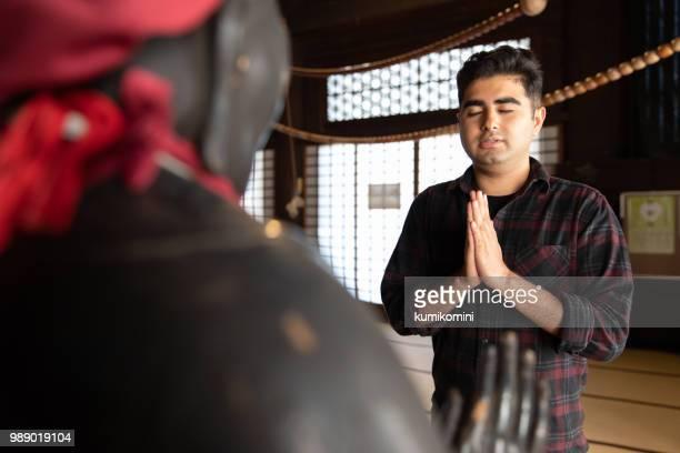 Asian man praying at temple