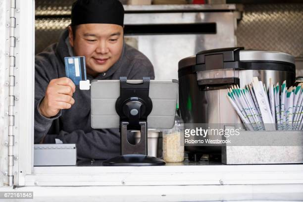 Asian man processing credit card using digital tablet at food cart