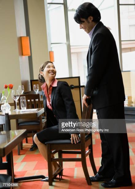 Asian man pushing in chair for girlfriend