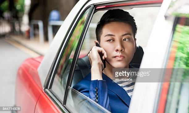 Asian Man Receiving An Upsetting Call In Taxi