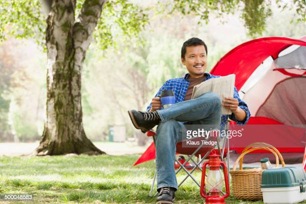 Asian man relaxing in lawn chair at campsite
