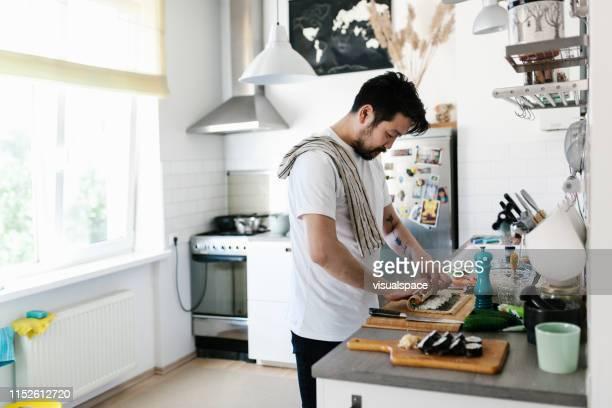 asiatischer mann rollen maki sushi - weitwinkel stock-fotos und bilder