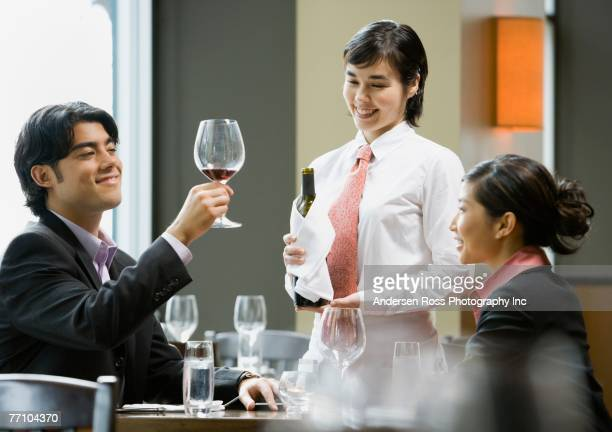 Asian man sampling wine at restaurant