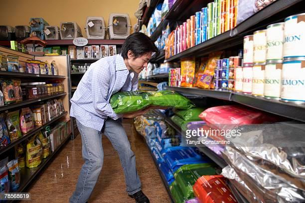 Asian man shopping for pet food