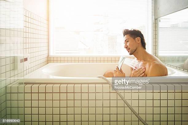 Asian man showering in Japanese bathtub
