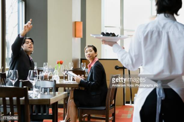 Asian man signaling restaurant server