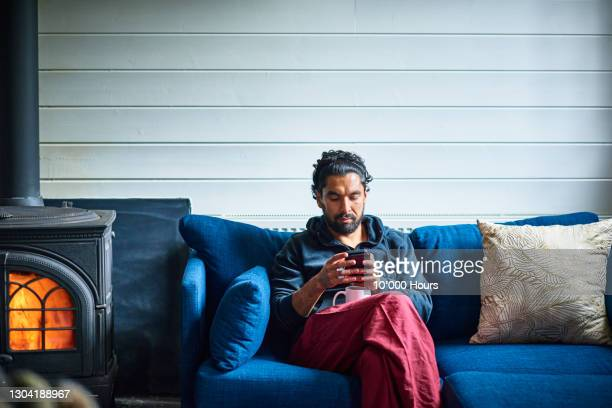 asian man sitting by fire checking mobile phone - one mid adult man only stock pictures, royalty-free photos & images