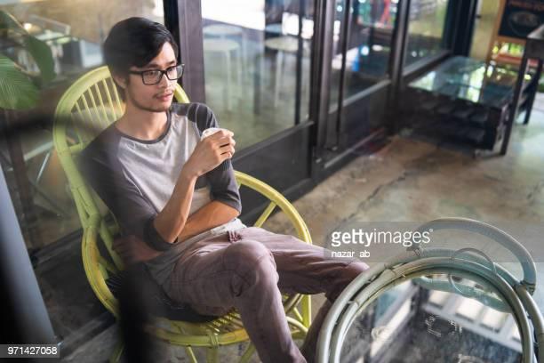 Asian man sitting in cafe during break.