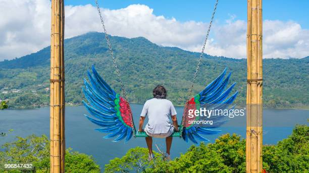 Asian man sitting on a swing looking at distance. Bali, Indonesia