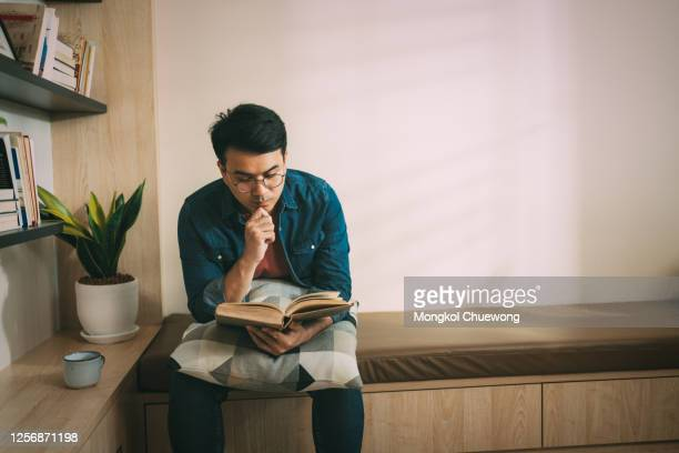 asian man sitting on sofa reading book at home - place of worship stock pictures, royalty-free photos & images
