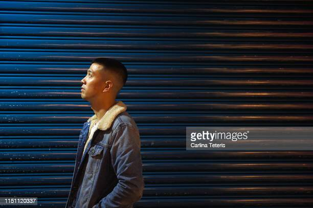 asian man standing against a metal wall at night - denim stock pictures, royalty-free photos & images