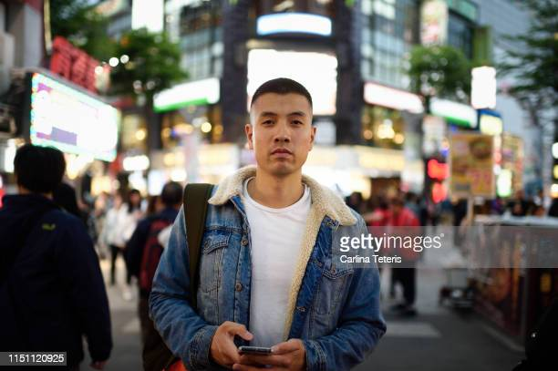 asian man standing in a busy market area at night - one night stand stock-fotos und bilder