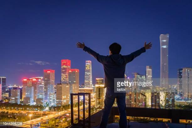 asiático homem em pé na frente da cidade moderna - evolução - fotografias e filmes do acervo