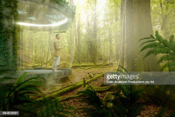 Asian man standing on patio in rain forest