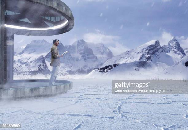 Asian man standing on patio in snow