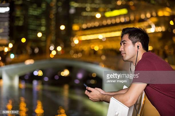 asian man standing outdoors with smart phone and earphones. - un seul homme d'âge moyen photos et images de collection