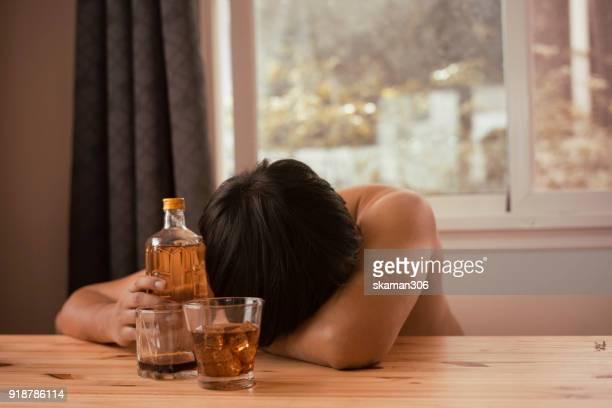 asian man stress and hand holding drink whiskey - koffie drank stockfoto's en -beelden
