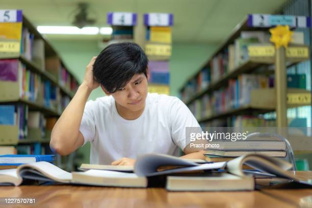 asian man student boring reading book at library with a lot of books in university. asian student disheartened reading book for examination - bad student stock pictures, royalty-free photos & images