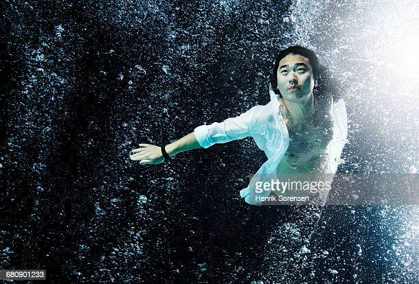 Asian man submersed in water