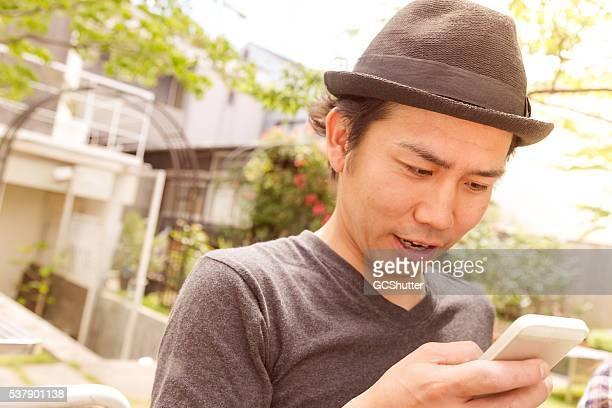 アジアの男性驚くリーティングからメッセージを友人