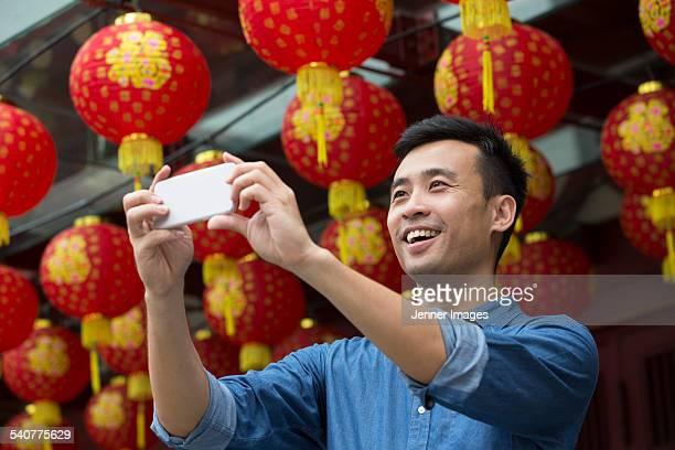 Asian Man taking photo with phone under lanterns