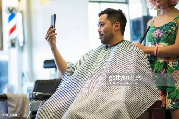 Asian man taking selfie of haircut in retro barbershop