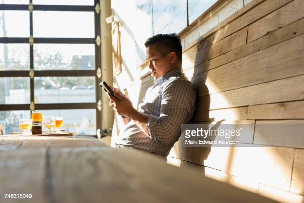 Asian man texting on cell phone in brew pub